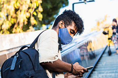 Young man wearing face mask using smart phone while standing on escalator - p300m2243327 by NOVELLIMAGE