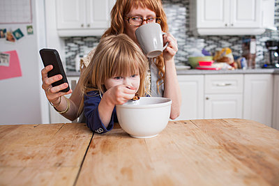 Girl eating breakfast, mother drinking coffee & looking at smartphone - p429m821912 by Hugh Whitaker