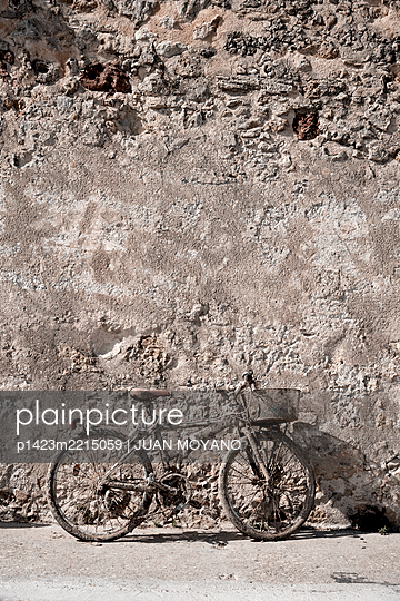Rusty bicycle against a rustic wall - p1423m2215059 by JUAN MOYANO