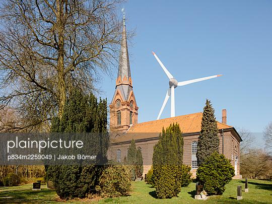 Germany, Hamburg, Altenwerder, St. Gertrud Church and wind turbine - p834m2259049 by Jakob Börner