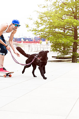 Skateboarder with dog - p1076m907871 by TOBSN