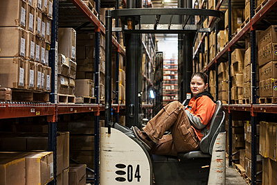 Caucasian female warehouse worker sitting in a motorized stock picker surrounded by products stored in cardboard boxes in a large warehouse distribution facility. - p1100m1575475 by Mint Images