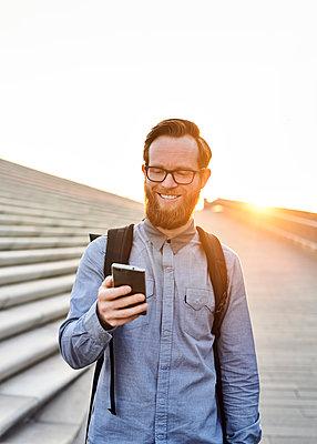 Mann mit Smartphone im Gegenlicht - p1124m1169969 von Willing-Holtz