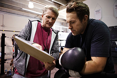 Trainer with clipboard talking to male boxer in gym - p1192m2033897 by Hero Images