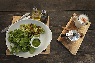 Salad and coffee served on a wooden board in a coffee shop - p1315m2003111 by Wavebreak