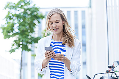 Smiling blond businesswoman using smartphone - p300m2023856 by Tom Chance