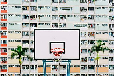 China, Hong Kong, Kowloon, basketball hoop, public housing in the background - p300m2059958 von Gemma Ferrando