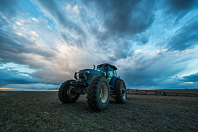 Tractor parked in a field under a dramatic sky at sunset; Val Marie, Saskatchewan, Canada  - p442m1523977 by Robert Postma