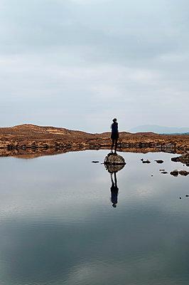 Frau auf einem Felsen im See - p470m1502266 von Ingrid Michel