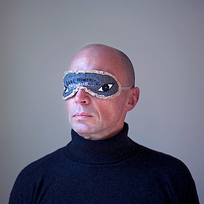 Head and Shoulders Portrait of Man Wearing Eye Mask - p694m2145275 by Novo Images