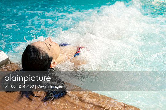 Hispanic woman enjoying the whirlpool in a spa - p1166m2147499 by Cavan Images