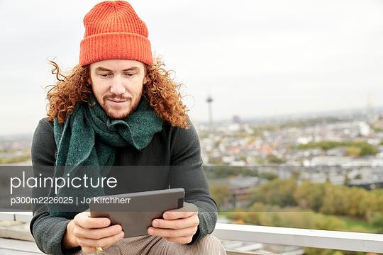 Man using digital tablet while sitting on building terrace against sky - p300m2226025 by Jo Kirchherr