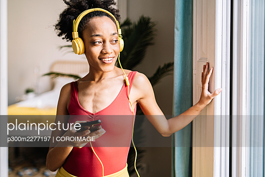 Beautiful woman listening music while looking through window at home - p300m2277197 by COROIMAGE