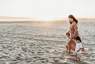 Side view of mother walking toddler twins to ocean with sun setting - p1166m2165866 by Cavan Images