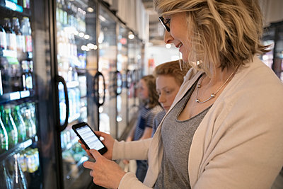 Mother with smart phone list grocery shopping in refrigerated market aisle - p1192m1567199 by Hero Images