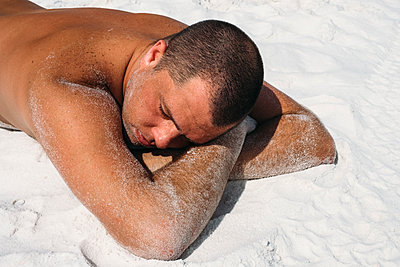 Man laying on a white sand beach in Florida - p1262m1584287 by Maryanne Gobble