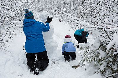 Father with children making snowman - p1315m1421995 by Wavebreak