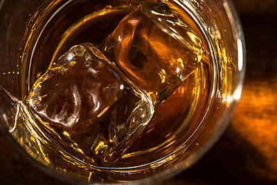 Glass of whiskey with ice cube - p1427m2169141 by Tetra Images