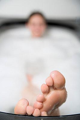 Woman lying in bathtub with feet resting on the edge - p3013863f by Stella