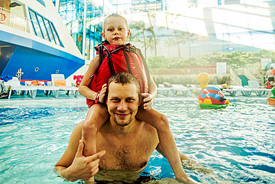 Caucasian father and son swimming in pool - p555m1306023 by Aleksander Rubtsov