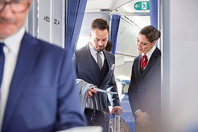 Flight attendant helping businessman with boarding pass on airplane - p1023m1519954 by Agnieszka Olek