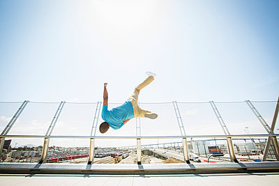 Young man somersaulting on a bridge.  - p1100m1038919 by Mint Images