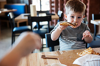 Portrait of cute boy eating pizza at restaurant - p1166m1144694 by Cavan Images
