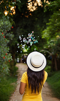 Rear view of woman in sun hat blowing bubbles on footpath - p1166m1163970 by Cavan Images