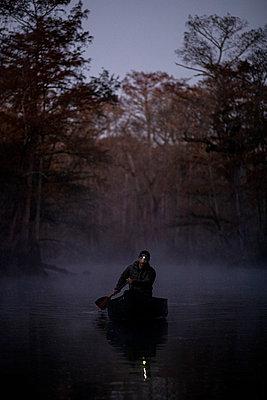 Sunrise canoe ride on foggy river. - p1166m2269645 by Cavan Images