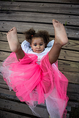 Little girl in pink tulle skirt lying on back - p1640m2246848 by Holly & John