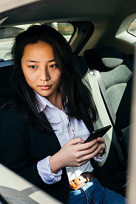 Portrait of pensive businesswoman with mobile phone sitting in a car looking at distance - p300m2189295 by Xavier Lorenzo