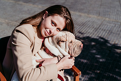 Young beautiful woman embracing pet at sidewalk cafe - p300m2281641 by Eva Blanco