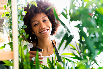 Afro woman gardening in a plant laboratory or shop, small business owner - p300m2287450 von Giorgio Fochesato