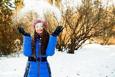 Caucasian girl throwing snow field - p555m1413188 by Aleksander Rubtsov
