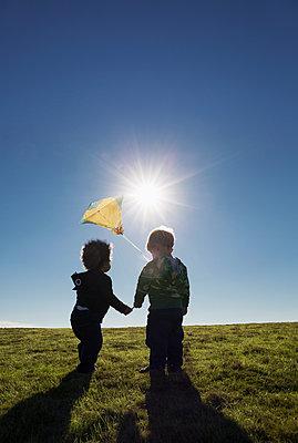 Boys watching kite flying against blue sky - p555m1419116 by Roberto Westbrook