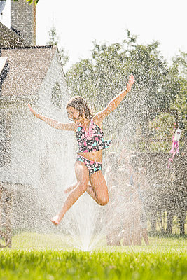 Girl jumping in sprinkler - p9246577f by Image Source