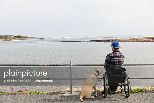 Disabled man in a wheelchair enjoying a day out - p1315m2162379 by Wavebreak