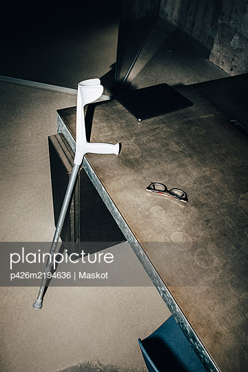 High angle view of crutch by eyewear on table at workplace - p426m2194636 by Maskot