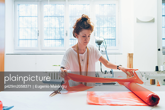 Fashion designer unrolling textile on workbench - p429m2058371 by Eugenio Marongiu