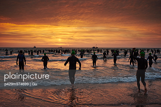 Crowd of silhouetted swimmers running into sea at sunrise, Tenby, Wales, UK