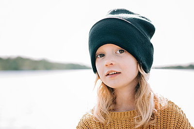 portrait of a young girl stood at the beach with a beanie on - p1166m2213120 by Cavan Images