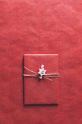 Wrapped Christmas present on a matching red background - p301m2039639 by Alexandra C. Ribeiro