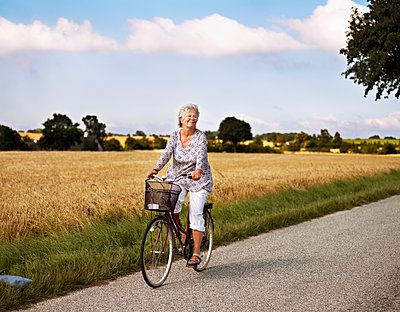 Woman cycling on rural road - p312m2200025 by Pernille Tofte