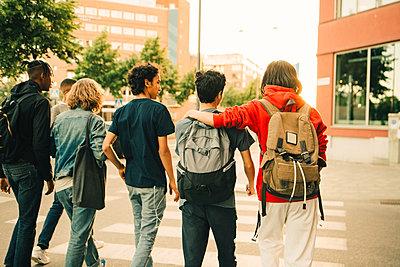 Rear view of male friends crossing road side by side in city - p426m2074916 by Maskot