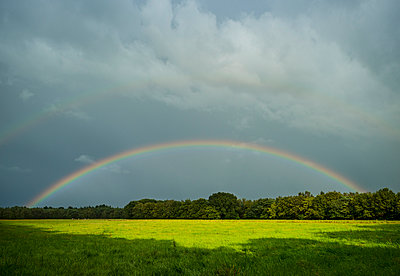 Storm clouds and rainbow over field landscape, Breda, Noord-Brabant, the Netherlands - p429m958548f by Mischa Keijser