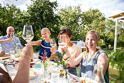 Friends toasting white wine  - p788m1165354 by Lisa Krechting