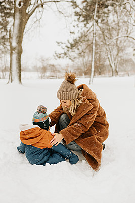 Canada, Ontario, Mother and baby boy (12-17 months) playing in snow - p924m2271228 by Sara Monika