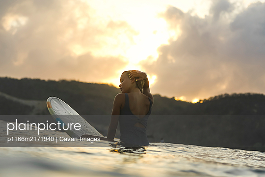 Female surfer in the ocean at sunset - p1166m2171940 by Cavan Images
