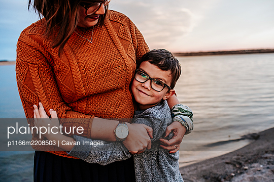 Mom hugging young son on the shore of a lake on a autumn evening - p1166m2208503 by Cavan Images
