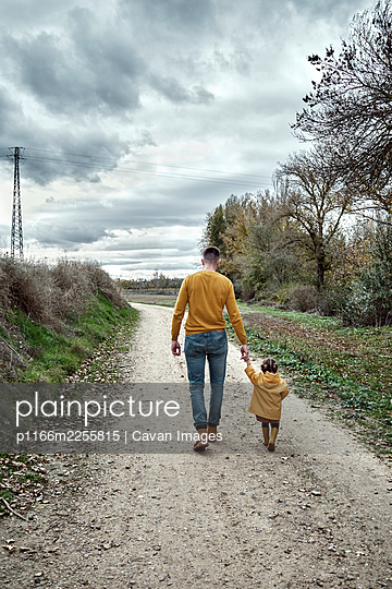 A two year old girl walking with her dad - p1166m2255815 by Cavan Images